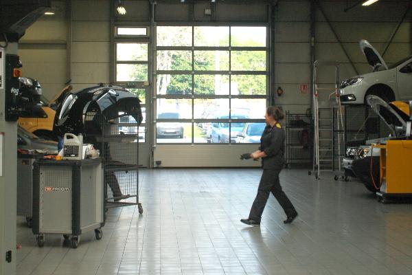 Laurine traverse l'atelier.